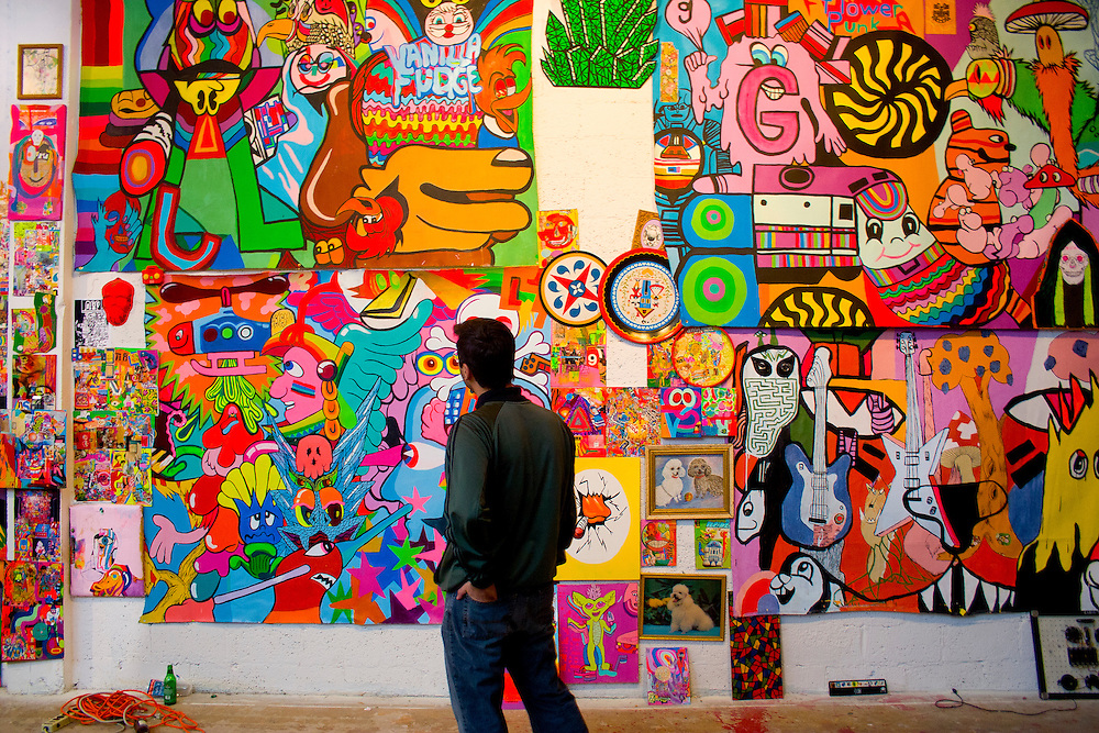 At a satellite art show in Miami's Design District during Miami Art Week 2004, a visitor studies a highly detailed mural by a Virginia-based artists collective named Dearraindrop.