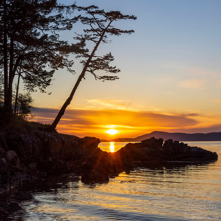 The setting sun shines through a break in the clouds over the San Juan Islands, casting its glint across the waters of Rosario Strait as seen from Sunset Beach on Fidalgo Island in Anacortes, Washington.