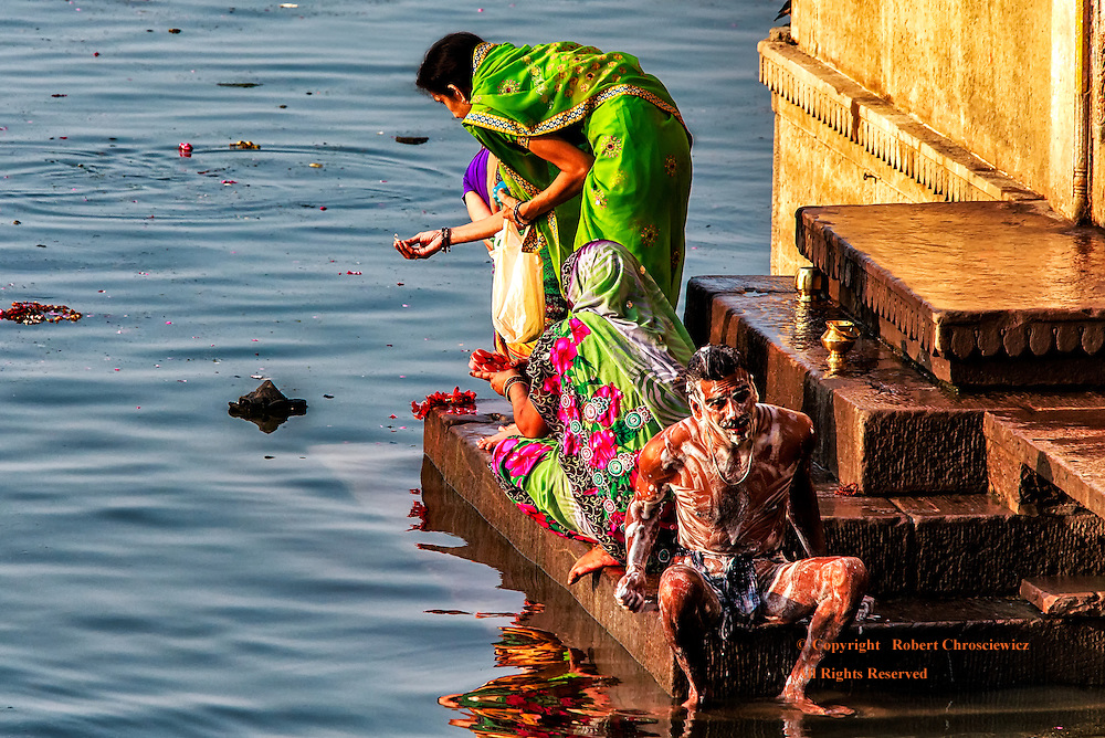 Cleansing Body and Soul: On the Ganges River one is never surprised to see the unexpected, such as these three Hindu women worshipers, in the midst of making offerings, sharing a small stairway with a man fully lathered and enjoying a bath, Varanasi India.