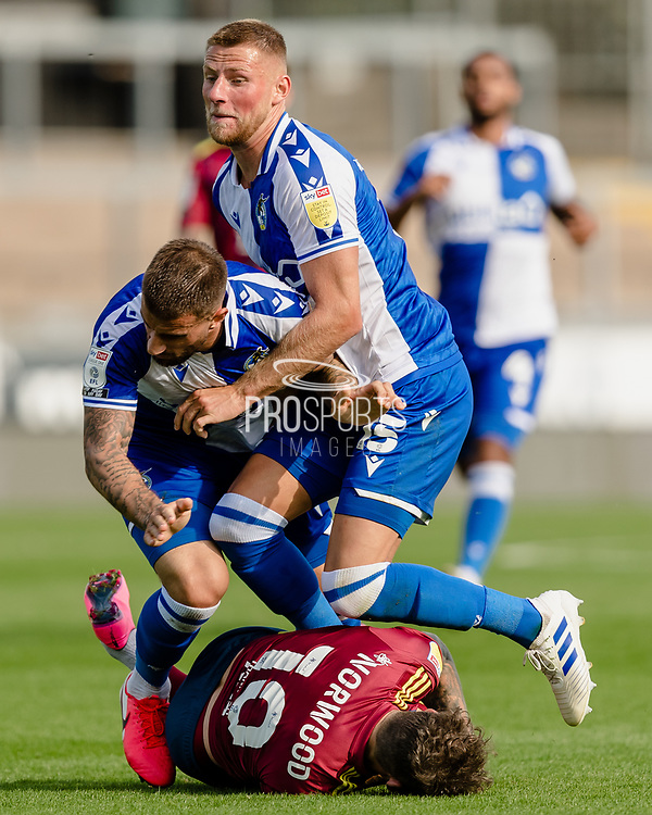Bristol Rovers defender Max Ehmer (5) and Bristol Rovers defender Alfie Kilgour (15) both take out Ipswich Town forward James Norwood (10) during the EFL Sky Bet League 1 match between Bristol Rovers and Ipswich Town at the Memorial Stadium, Bristol, England on 19 September 2020.