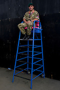 One of the 18,000 British soldiers of the Royal Marines sits in a Games Maker's high chair to oversee an entrance to the Olympic Park during the London 2012 Olympics. A total of 18,000 defence personel were called upon to make the Games secure following the failure by security contractor G4S to provide enough private guards. This land wastransformed to become a 2.5 Sq Km sporting complex, once industrial businesses and now the venue of eight venues including the main arena, Aquatics Centre and Velodrome plus the athletes' Olympic Village. After the Olympics, the park is to be known as Queen Elizabeth Olympic Park.