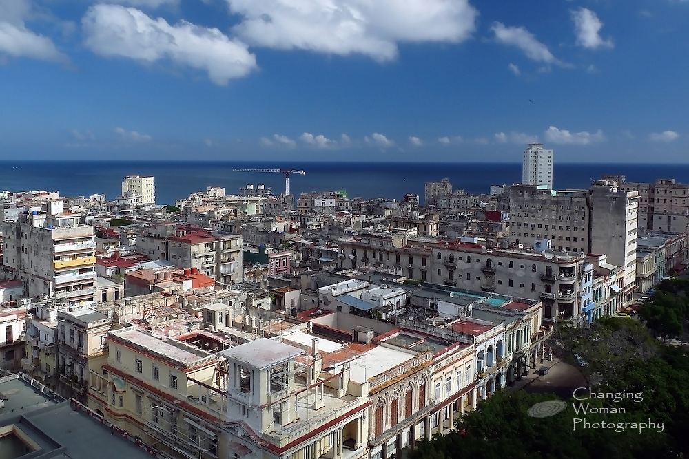 A view of Old Havana from an upper floor of the Hotel Sevilla features the tree-lined El Prado in the lower right corner lined by the Paseo del Prado's historic buildings now housing shops, restaurants, etc. Scattered among the bright colors and vintage architecture the viewer may note signs of reconstruction in the scaffolding attached to various buildings and the tall construction crane in the middle distance.