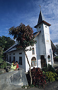 Batak Christian church..Batak Indigenous Christian people living on Samosir Island and nearby Lake Toba in Indonesia. There are some 6 million Christian Batak in Indonesia, the world's largest Muslim country of 237 million people, which has more Muslims than any other in the world. Though it has a long history of religious tolerance, a small extremist fringe of Muslims have been more vocal and violent towards Christians in recent years. ..Batak religion is found among the Batak societies around Lake Toba in north Sumatra. It is ethnically diverse, syncretic, liable to change, and linked with village organisations and the monotheistic Indonesian culture. Toba Batak houses are boat-shaped with intricately carved gables and upsweeping roof ridges, and Karo Batak houses rise up in tiers. Both are built on piles and are derived from an ancient Dong-Son model. The gable ends of traditional houses, Rumah Bolon or Jabu, are richly decorated with the cosmic serpent Naga Padoha carved in wood or in mosaic, lizards, double spirals, female breasts, and the head of the singa, a monster with protruding eyes that is part human, part water buffalo, and part crocodile or lizard. The layout of the village symbolises the Batak cosmos. They cultivate irrigated rice and vegetables. Irrigated rice cultivation can support a large population, and the Toba and the Karo live in densely clustered villages, which are limited to around ten homes to save farming land. The kinship system is based on marriage alliances linking lineages of patrilineal clans called marga. In the 1820's Islam came to the southern Angkola and Mandailing homelands, and in the 1850's and 1860's Christianity arrived in the Angkola and Toba region with Dutch missionaries and the German Rheinische Mission Gesellschaft. The first German missionary caused the Dutch to stop Batak communal sacrificial rituals and music, which was a major blow to the traditional religion. Dutch colonial policy favoured Christian villages. In 19