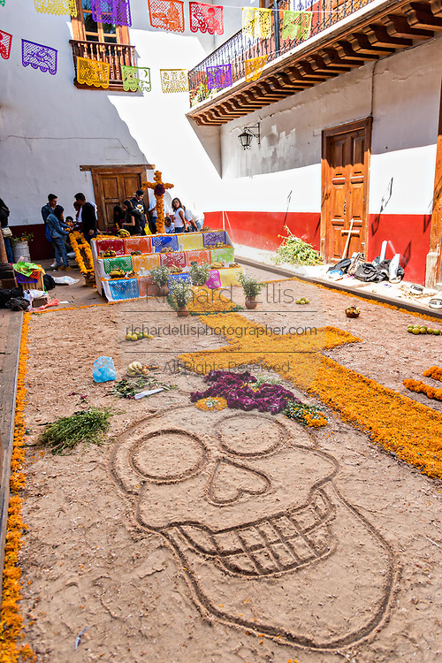 A skull in sand part of a giant ofrenda with colorful marigolds for the Day of the Dead festival in Patzcuaro, Michoacan, Mexico.