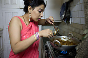 An Indian housewife at home in New Delhi, cooks her favourite dish in her kitchen, New Delhi, India