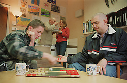 Residents playing game of back gammon in communal lounge of homeless hostel for people with learning difficulties,