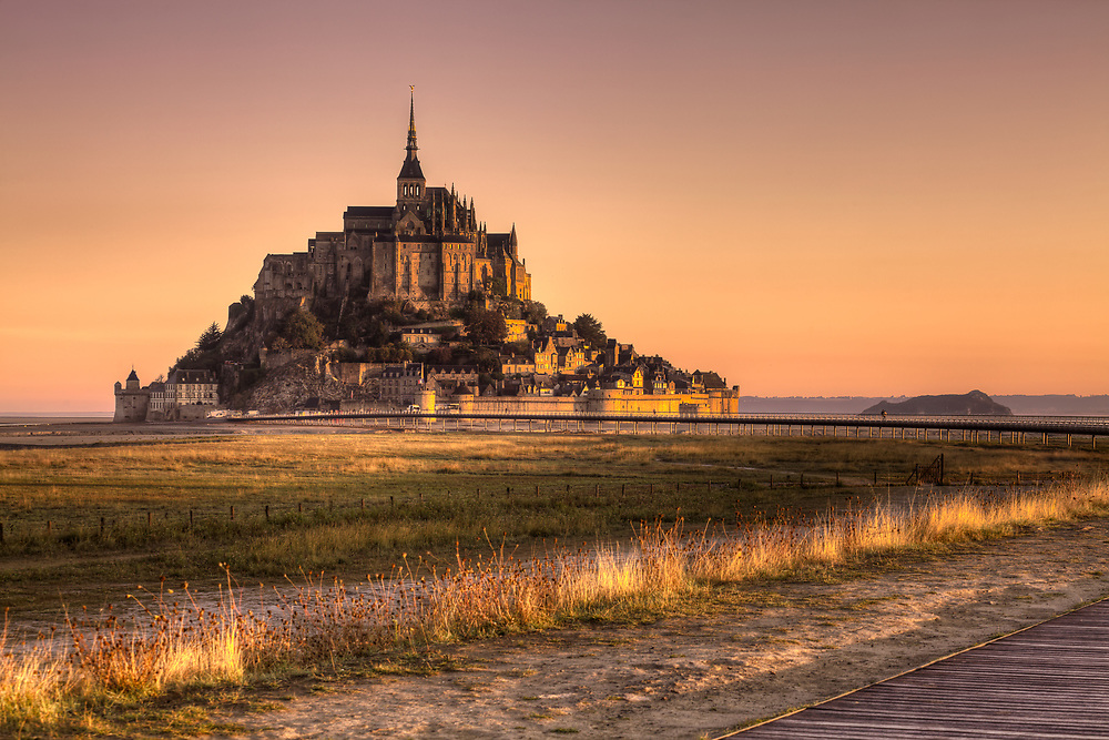 Le Mont-Saint-Michel is a tidal island and mainland commune in Normandy, France.<br /> <br /> The island is located about one kilometer (0.6 miles) off the country's northwestern coast, at the mouth of the Couesnon River near Avranches and is 7 hectares (17 acres) in area. The mainland part of the commune is 393 hectares (971 acres) in area so that the total surface of the commune is 400 hectares (988 acres).<br /> <br /> As of 2015, the island has a population of 50.