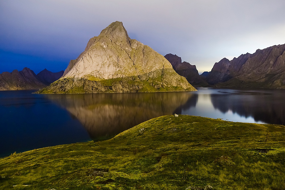 A mountain glows at night, lit by the lights of nearby Reine, Moskenesoya, Lofoten Islands, Norway.
