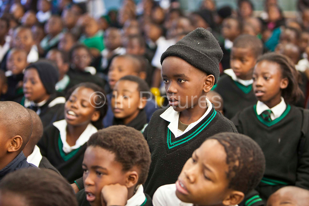 """Children from Ithute primary school in the Alexandra Township, Johannesburg, South Africa, watch a performance of the 'About Us"""", an AREPP: Theatre for Life production providing interactive social life skills education to school children through theatre productions. They are based in Johannesburg, South Africa and are on tour for 3 months doing performances everyday at schools across the country."""