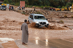 Man observing vehicle at river crossing during flood at Ait Snan on road to Todra Gorge, Morocco