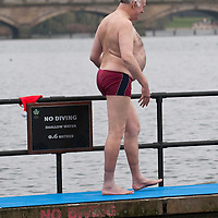 LONDON, ENGLAND - DECEMBER 25:  A member of the Serpentine Swimming Club gets ready to swim in the icy Serpentine waters during the annual Christmas Day Peter Pan Cup on December 25, 2009 in London, England.  The traditional 100 yards Christmas race got its name in 1904 after Sir James Barrie presented the first Peter Pan Cup and is only open to club members who have competed in at least three of the winter series races.  (Photo by Marco Secchi/Getty Images)