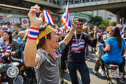 """20 DECEMBER 2013 - BANGKOK, THAILAND:  Anti-government protestors dance on Silom Road. Thousands of anti-government protestors, supporters of the so called Peoples Democratic Reform Committee (PRDC), jammed the Silom area, the """"Wall Street"""" of Bangkok, Friday as a part of the ongoing protests against the caretaker government of Yingluck Shinawatra. Yingluck dissolved the Thai Parliament earlier this month and called for national elections on Feb. 2, 2014. The protestors want the elections postponed and the caretaker government to step down. The Thai election commission ruled Friday that the election would go on dispite the protests.         PHOTO BY JACK KURTZ"""