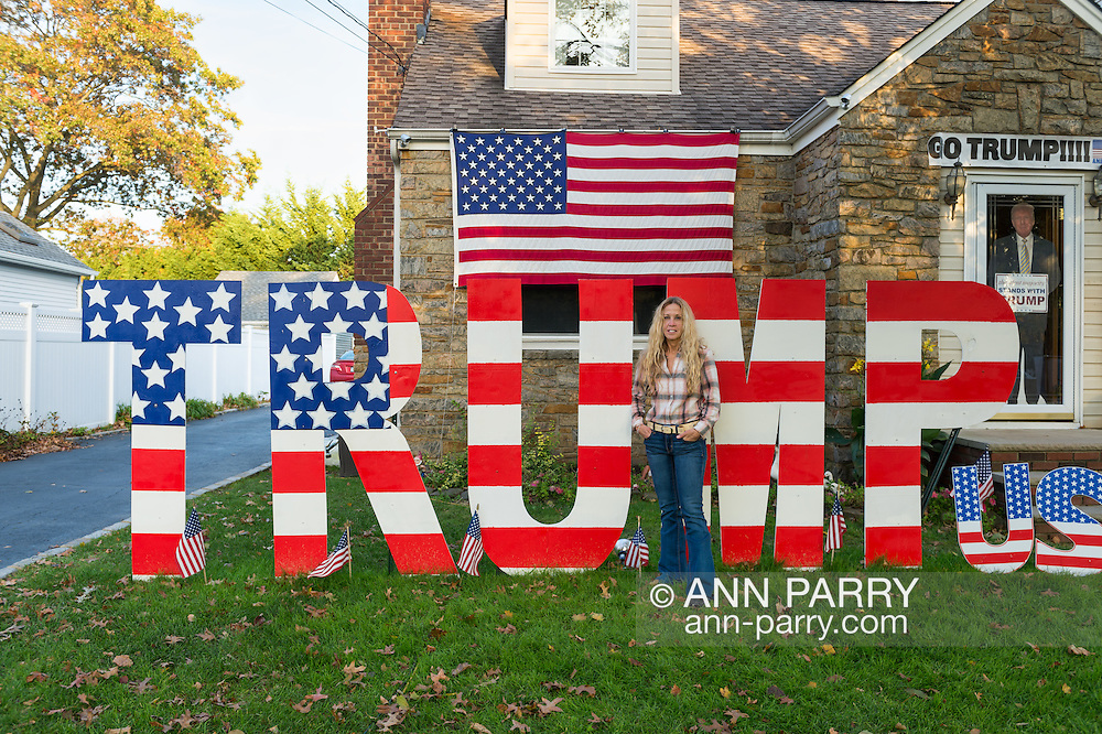 """Bellmore, New York, USA. November 2, 2016. EILEEN FUSCALDO, a Donald Trump Supporter, stands in front of TRUMP display, one of many in her front yard for the Republican presidential candidate, D. J. Trump, and against Democratic one, H. R. Clinton.  On her front door is a life-size cardboard Trump holding """"The Silent Majority Stands with Trump"""" sign."""