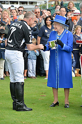 LYNDON LEA receives the Cartier Queen's Cup from HM THE QUEENat the Cartier Queen's Cup Final polo held at Guards Polo Club, Smith's Lawn, Windsor Great Park, Egham, Surrey on 15th June 2014.