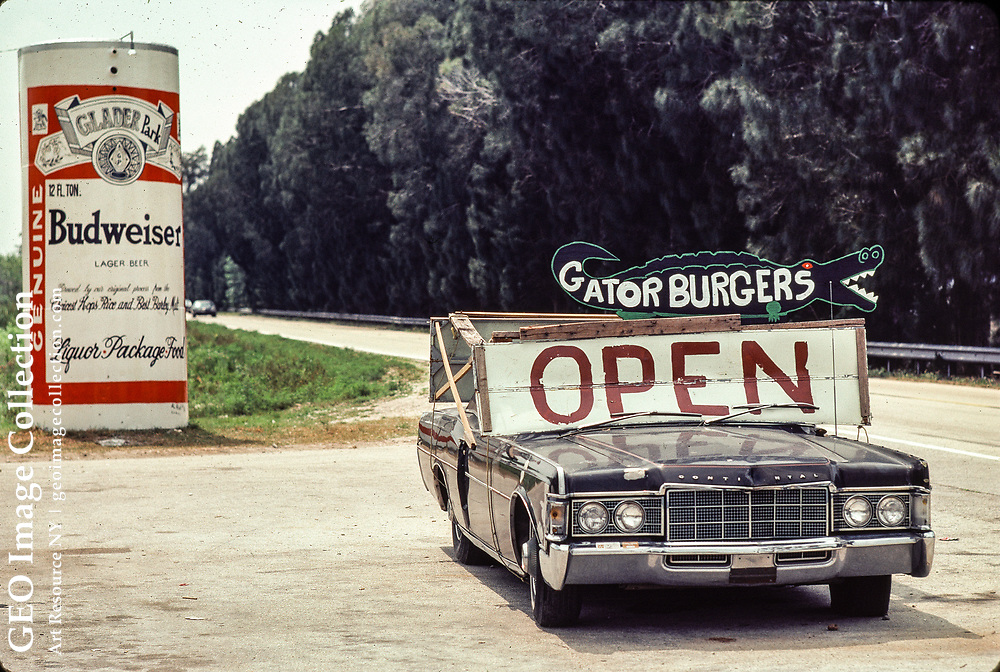 Roadside sign offering gatorburgers, ground meat made from alligator reptiles that are native to the Everglades. Also, a giant Budweiser beer can. The sign is mounted on a Lincoln Continental. The area is Tamiami Trail in the Everglades and many tourists pass.