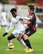 Wilfried Bony of Swansea city holds off Joey Barton of QPR. Barclays Premier league match, Swansea city v Queens Park Rangers at the Liberty stadium in Swansea, South Wales on Tuesday 2nd December 2014<br /> pic by Andrew Orchard, Andrew Orchard sports photography.