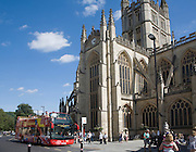 Tower of Bath abbey church with red double decker tour bus, Bath, Somerset, England