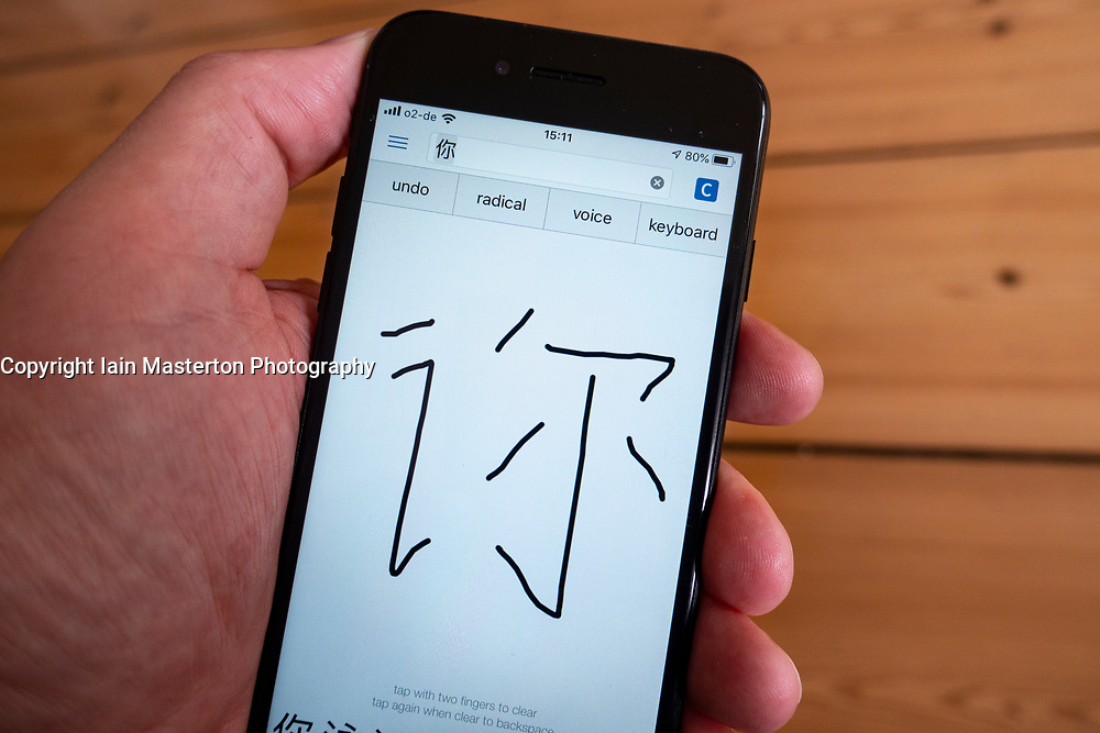Detail of language translation app  showing handwritten input of Chinese character on a smart phone screen