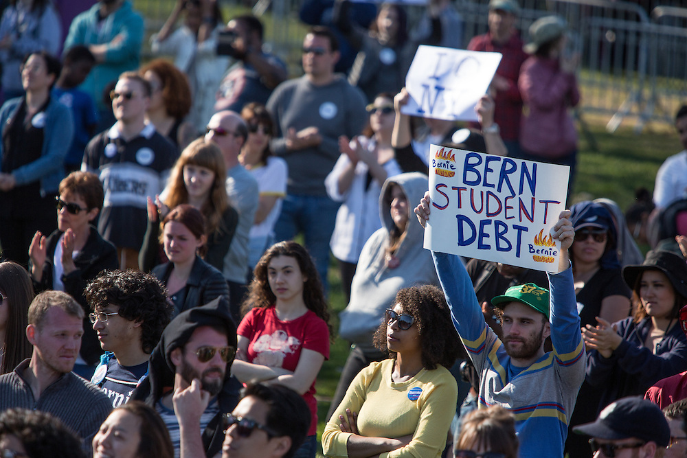 """Brooklyn, NY - 17 April 2016. A man holds a sign reading """"Bern studet debt."""" Vermont Senator Bernie Sanders, who is running as a Democrat in the U.S. Presidential primary elections, held a campaign """"get out the  vote"""" rally in Brooklyn's Prospect Park."""