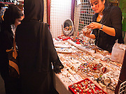 06 JULY 2011 - BANGKOK, THAILAND: A Thai women sells novelty jewelry to Arab women in the Soi Arab section of Bangkok. Soi Arab is an alleyway in Bangkok. What started as an alley has now grown into a neighborhood that encompasses several blocks of restaurants, hotels and money exchanges that cater to Middle Eastern visitors to Thailand. The official name of the street is Sukhumvit Soi 3/1, located in North Nana between Sukhumvit Soi 3 and Sukhumvit Soi 5, not far from the Nana Plaza night-life area and the Grace Hotel popular among Arabs.   PHOTO BY JACK KURTZ