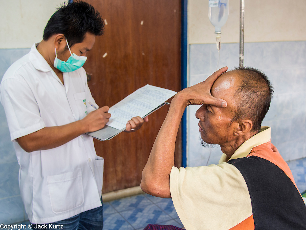 05 MARCH 2014 - MAE SOT, TAK, THAILAND: A patient describes his headaches to a medic at the Mae Tao Clinic. The Mae Tao Clinic provides  healthcare to over 150,000 displaced Burmese per year and is the leading healthcare provider for Burmese along the Thai-Myanmar border. Reforms in Myanmar have alllowed NGOs to operate in Myanmar, as a result many NGOs are shifting resources to operations to Myanmar, leaving Burmese migrants and refugees in Thailand vulnerable.     PHOTO BY JACK KURTZ