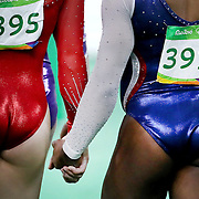 Gymnastics - Olympics: Day 6  Alexandra Raisman, (left), of the United States and Simone Biles of the United States hold hands as they walk to the final apparatus during the Artistic Gymnastics Women's Individual All-Around Final at the Rio Olympic Arena on August 11, 2016 in Rio de Janeiro, Brazil. (Photo by Tim Clayton/Corbis via Getty Images)