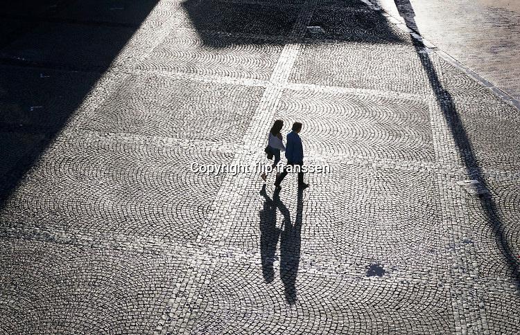 Nederland, Groningen, 20-8-2018 Plein waar mensen onherkenbaar met hoog contrast in tegenlicht en met een langgerekte schaduw overheen lopen . Foto: Flip Franssen