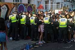 London, August 29th 2016. Police form a cordon to prevent more people making their way onto the dangerously crowded Ladbroke Grove during day two of Europe's biggest street party, the Notting Hill Carnival.