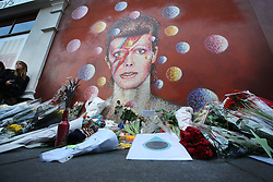 © Licensed to London News Pictures. 11/01/2016. London, UK. Flowers, cards, candles and other tributes have been placed below a mural of David Bowie in Brixton. The Death of David Bowie, who was born in Brixton, has been announced today.  Photo credit: Peter Macdiarmid/LNP