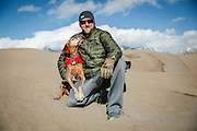 SHOT 12/30/15 1:52:16 PM - Marc Piscotty of Denver, Co. pauses for a picture with his dog, Tanner, an 11 year-old male Vizsla, at Great Sand Dunes National Park and Preserve. Great Sand Dunes is a U.S. National Park located in the San Luis Valley, in the easternmost parts of Alamosa County and Saguache County, Colorado, United States. Originally created as Great Sand Dunes National Monument on March 17, 1932, Great Sand Dunes National Park and Preserve was established by an act of the United States Congress on September 13, 2004. The park contains the tallest sand dunes in North America, rising about 750 feet (230 m) from the floor of the San Luis Valley on the western base of the Sangre de Cristo Range, covering about 19,000 acres. Researchers say that the dunes started forming less than 440,000 years ago. The dunes were formed from sand and soil deposits of the Rio Grande and its tributaries, flowing through the San Luis Valley. Over the ages, glaciers feeding the river and the vast lake that existed upon the valley melted, and the waters evaporated. Westerly winds picked up sand particles from the lake and river flood plain. As the wind lost power before crossing the Sangre de Cristo Range, the sand was deposited on the east edge of the valley. This process continues, and the dunes are slowly growing. The wind changes the shape of the dunes daily. (Photo by Marc Piscotty / © 2015)