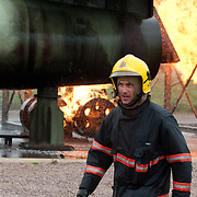 Fire fighter with dramatic flames in background.
