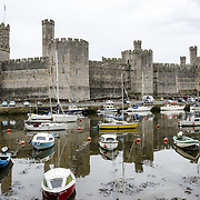 A view of the castle from across the river, with boats moored in the foreground, at Caernarfon Castle in northwest Wales. A castle originally stood on the site dating back to the late 11th century, but in the late 13th century King Edward I commissioned a new structure that stands to this day. It has distinctive towers and is one of the best preserved of the series of castles Edward I commissioned.