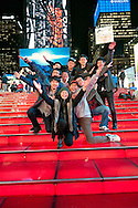 Group of friends having fun on big TKTS Red Stairway at Times Square Duffy Square in Manhattan, New York, USA, night of  January 9, 2012