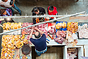 View looking down on a butcher serving customers in the vast Mercado Hidalgo, a public market inside a former train station in the historic center of Guanajuato City, Guanajuato, Mexico.