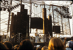 Grateful Dead Live at Dillon Stadium, Hartford, CT 31 July 1974 featuring the Wall of Sound. Almost full band photo, Keith is just out of the frame. Donna is not on stage. Centered to show the Sound System. Late afternoon lighting.