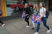 Three young woman carry Union Jack and Big Ben plastic shopping bags on Oxford Street, on 30th May 2019, in London, England.
