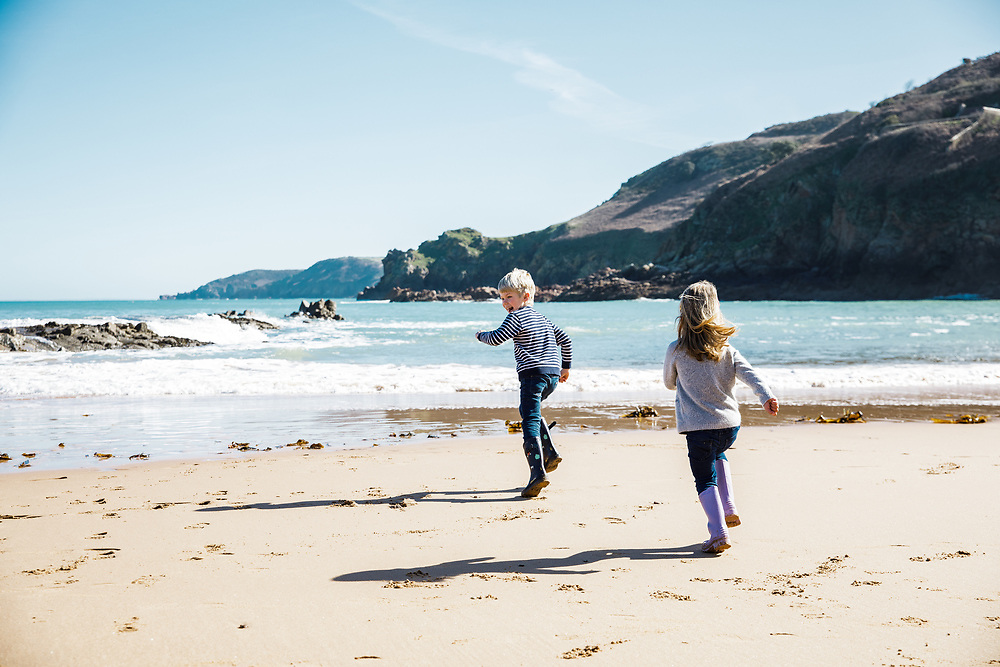 Boy and girl running after each other and playing on the sand at Greve de L'Ecq beach in Jersey, Channel Islands