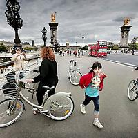 Frankrijk.Parijs.9 augustus 2007..Toeristen en Parijzenaren zie je steeds meer op de fiets de stad verkennen zoals hier op de brug Alexander III over de Seine. De meeste fietsen zijn te huur onder de naam Velib (zie foto) en in het centrum zijn verschillende Velib fietsverhuur plekken waar men d.m.v. een creditcard een fiets kan huren per half uur.