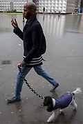 A dog walker passes the entrance of Elephant and Castle underground station, on 29th March, 2018 in London, England.