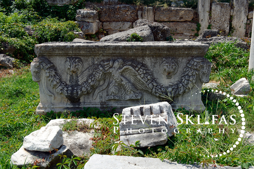 Athens. Greece. View of an ornately carved and crafted stone a sarcophagus looking water fountain. Water flowed through small holes found on all side of the sculpture. Dating from the 1st century BC, the Roman Agora is about 100 metres to the east of the Ancient Agora and is complex consisting of a large rectangular open courtyard surrounded by stoas, shops and storerooms.