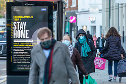 © Licensed to London News Pictures. 24/12/2020. London, UK. Christmas Eve shoppers in Chelsea, South West London walk past an NHS 'Stay Home' Tier 4 information sign while doing their last minute shopping. Yesterday, Health Secretary Matt Hancock announced that yet another new Covid-19 mutation has been discovered in the UK. While Downing Street has now ordered many more areas of England to go into Tier 4 lockdown from Boxing Day with tougher new Covid-19 restrictions for many as the mutated strains continue to spread throughout the South East. Photo credit: Alex Lentati/LNP