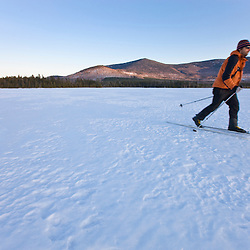 A man cross-country skis on First West Branch Pond at West Branch Pond Camps near Greenville, Maine.  White Cap Mountain is in the distance.