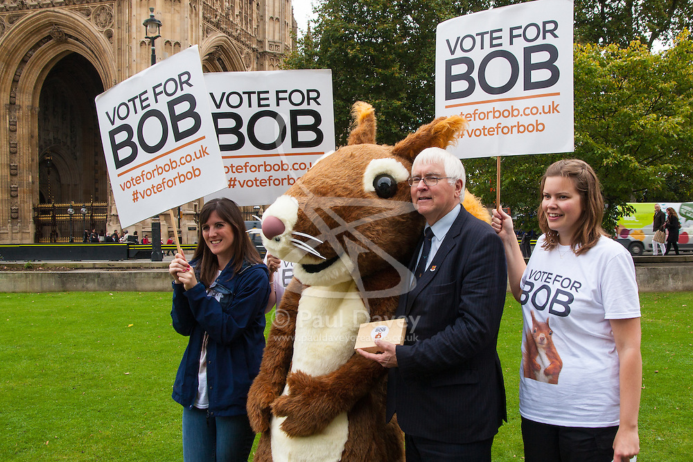 """Nature campaigners accompanied by a  giant red squirrel, Bob, urge MPs to """"Vote For Bob"""" during a photocall outside Parliament. Their aim is to get MPs to support nature in Britain. PICTURED: Sir Bob Russel MP holding a box of """"Bob's biscuits"""" poses with campaigners outside Parliament."""