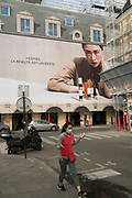 """March, 19th, 2020 - Paris, Ile-de-France, France: Paris Marais Hermes advertisement in Place des Vosges hoarding overshadows residents, on the third day of a near total lockdown imposed in France. All journeys outside the home unless justified for essential professional or health reasons are outlawed. Anyone flouting the new regulations is punished with monetary fines. French police control of citizens and inspection of valid papers allowing citizens to travel. The most extreme measures so far in France to control the spread of the Coronavirus. Earlier in the week, President of France, Emmanuel Macron, said that citizens must stay at home from midday on Tuesday for at least 15 days. He said """"We are at war, a public health war, certainly but we are at war, against an invisible and elusive enemy"""". Nigel Dickinson"""