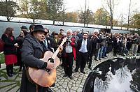 DEU, Deutschland, Germany, Berlin, 24.10.2012:<br />Feierliche Einweihung des Denkmals für die im Nationalsozialismus ermordeten Sinti und Roma Europas gegenüber dem Reichstag. Nach dem offiziellen Teil der Zeremonie greift einer der Gäste zur Gitarre und singt dazu ein Lied.