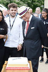 The Duke of Edinburgh admires a cake during a reception to celebrate the London Youth charity's 130th anniversary, at Buckingham Palace in London.