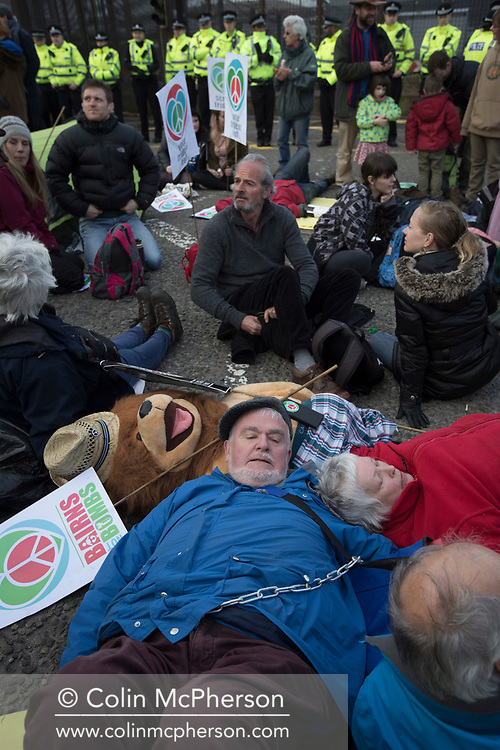 People staging a lie-down in front of a line of police officers at the North Gate of Her Majesty's Naval Base, Clyde, Faslane, Scotland, during a blockade by around 150 people protesting against the Trident nuclear missile system. The protestors managed to shut down the base, preventing workers, contractors and naval personnel from accessing the site. A decision was due to be made by the UK government in 2016 whether to replace the Trident submarine system.
