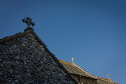 Three crosses on the nave roof of St. Benedict church, Horning on the Nofolk Broads. With the nearest side in shadow, we see the flint stones set into the building's walls. St. Benedict lies half a mile east of the village and dates back to the 13th Century. This area of Britain is known as East Anglia, once the stronghold of Saxon tribes then later, of Norse Vikings before Christianity dominated the religious landscape. Christian sites of worship were built on pagan shrines to encourage the following of the new God.