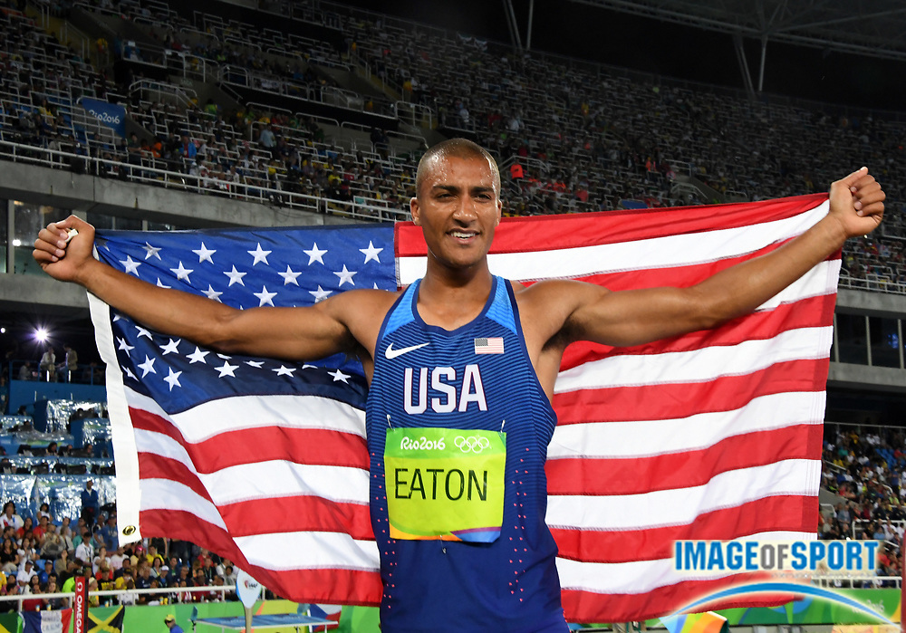 Aug 18, 2016; Rio de Janeiro, Brazil; Ashton Eaton (USA) poses with United States after tying an Olympic record to win the decathlon with 8,893 points during the 2016 Rio Olympics at Estadio Olimpico Joao Havelange.