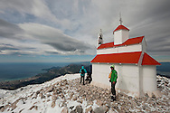 Hiking on Rumija, a mountain above Lake Skadar and Stari Bar, after October snowfall, Montenegro. The small metal Orthodox church was airlifted onto the summit in 2005. © Rudolf Abraham